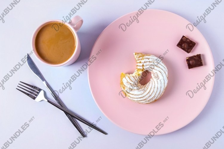 Bitten cake on a pink plate, cutlery and a cup of cocoa example image 1