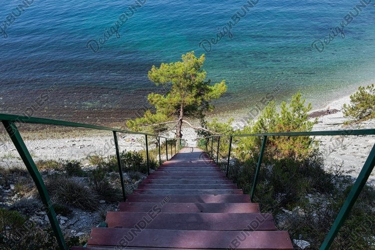 Stairs to the sea on the rocks leads to the beach. 3 pcs example image 1