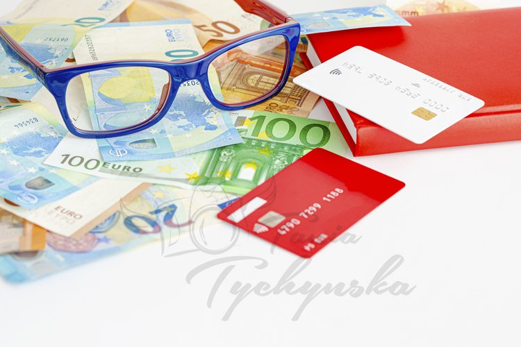 Glasses on euro currency, notebook and credit cards.