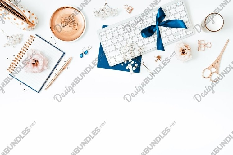 Flat lay with keyboard, gold and blue colored desk items