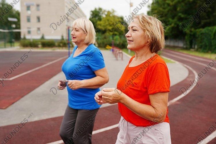 Beautiful adult women running outdoors on the stadium