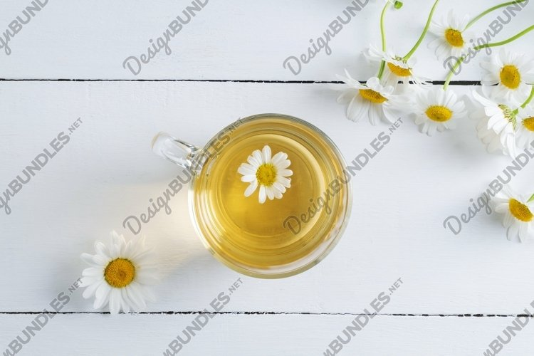 Close up top view of chamomile tea cup and flowers