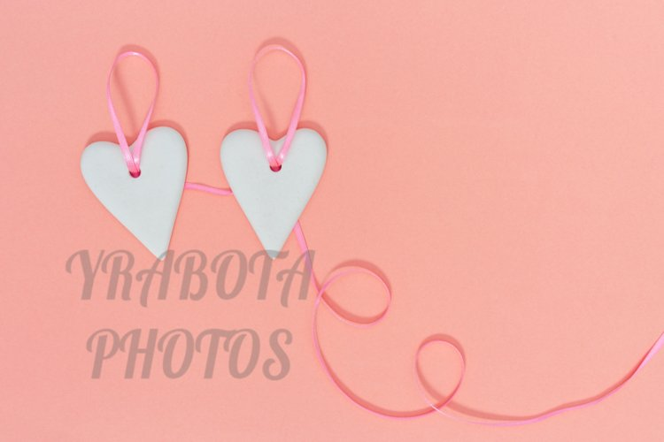 Two white hearts together on pink ribbon