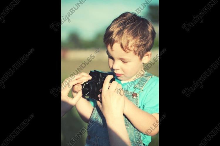 Mother helping her son to make his first photos example image 1