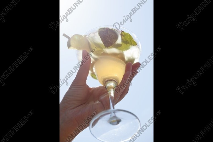 Female hand holding a cocktail example image 1