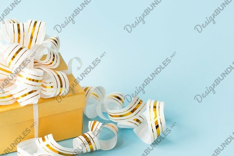 Golden gift box with golden ribbon on blue background example image 1