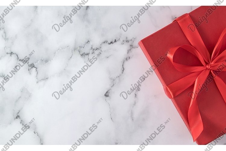 Red gift box with bow on marble with copy space example image 1
