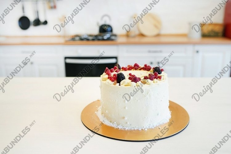 Delicious creamy cake with berries on white table example image 1