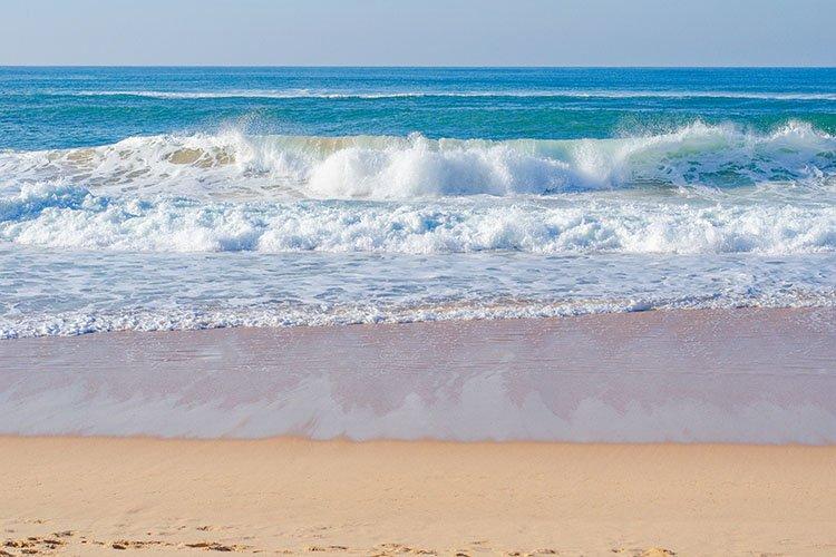 Picturesque beach, ocean waves run, footprints in the san.