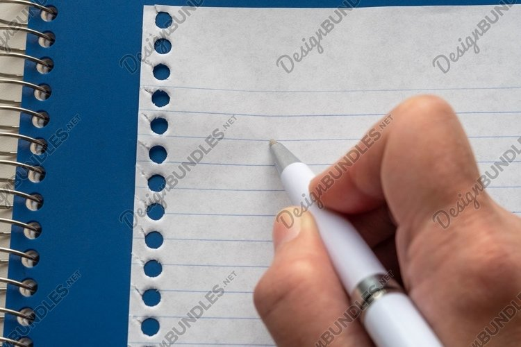 Hand writing with a white pen on page from blue notebook. example image 1