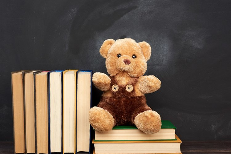 brown teddy bear sits on a brown wooden table example image 1