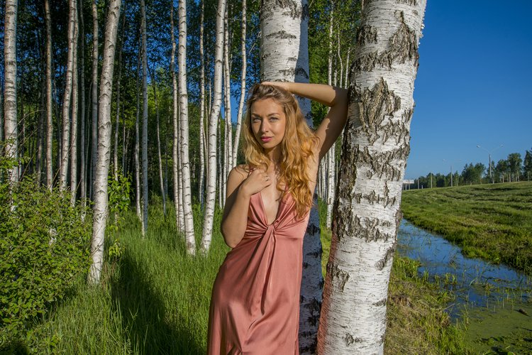Young slender beautiful girl in a long coral dress example image 1