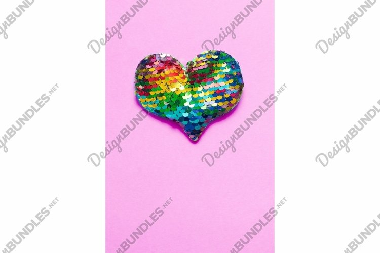 Colorful heart made of rainbow sequins on pink background
