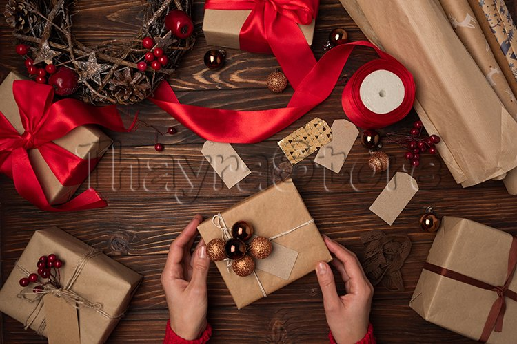 Female hands wrapping gift box on brown wooden table example image 1