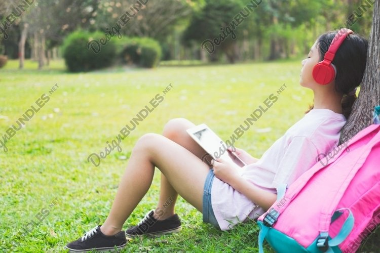 Girl with wireless headphones listens to the music in park. example image 1