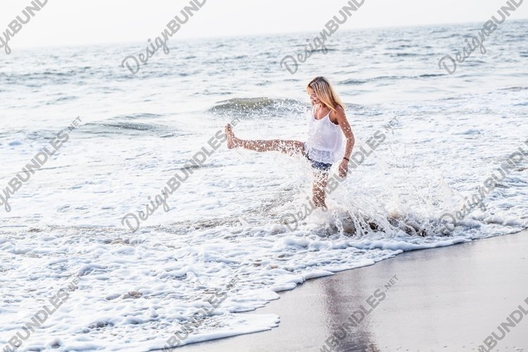 Attractive happy mature tourist woman jumping on sand beach. example image 1