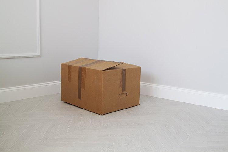 shabby cardboard box in the corner in an empty new room