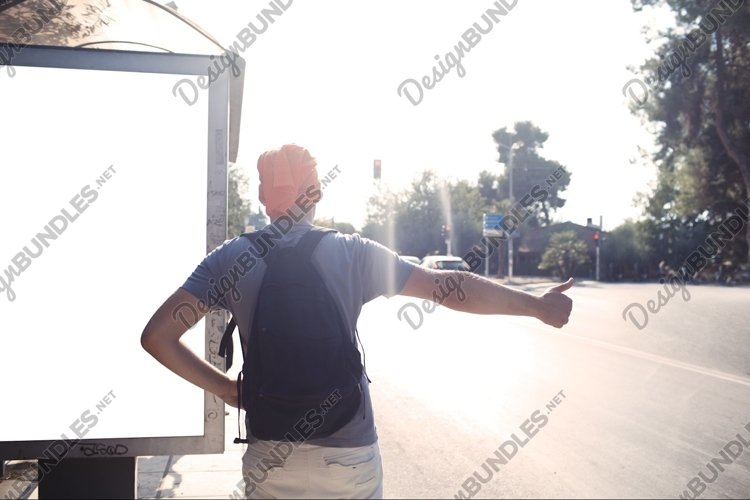 Man standing near bus stop thumbing a lift example image 1