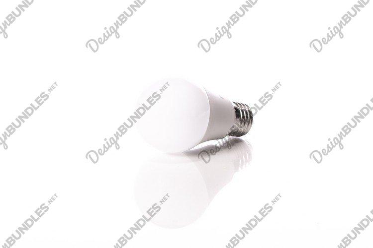 energy-saving LED light bulb lying on glass surface with ref example image 1