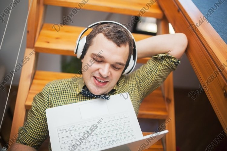 Man entertaining with laptop and music at home example image 1