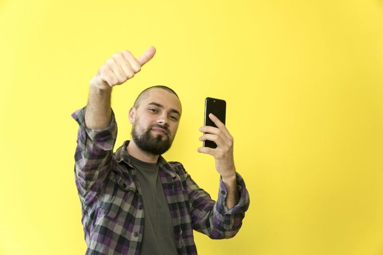 Young caucasian man with phone on yellow background example image 1