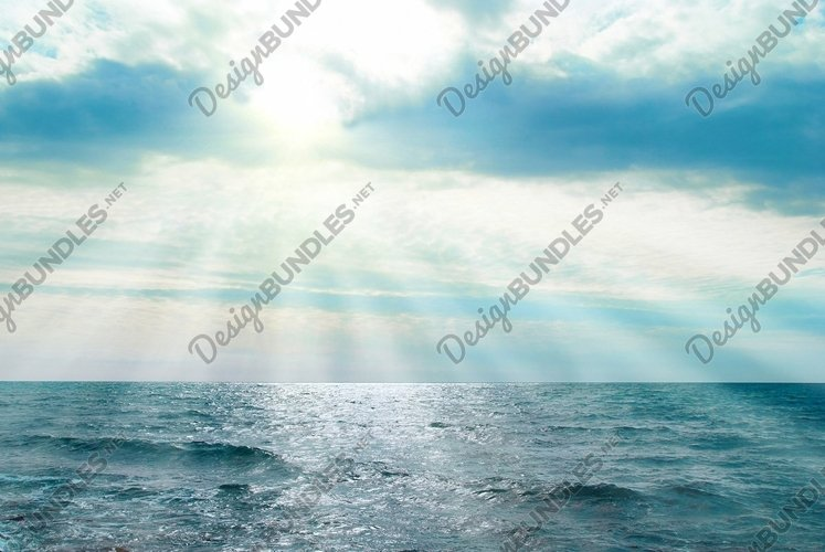 Water, waves and clouds. Sunset above the sea with sunbeams