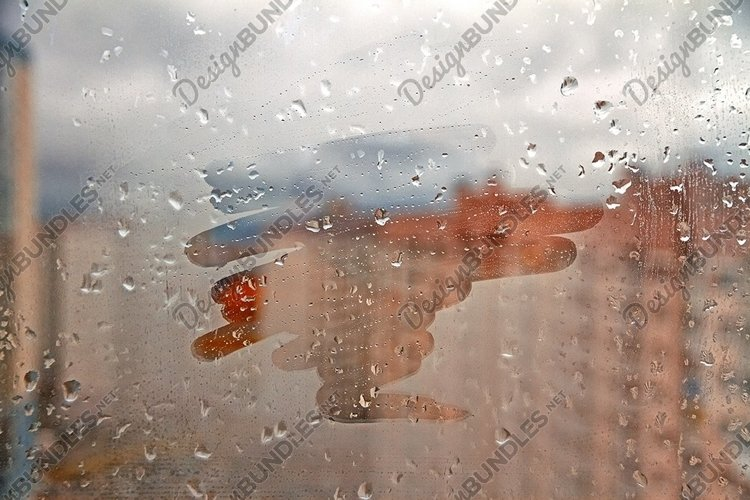 Blurred spot on foggy window spattered with drops in city example image 1
