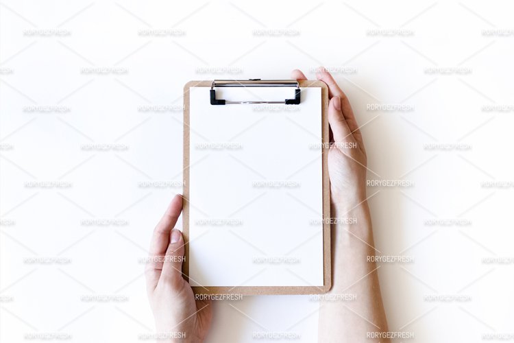 Girl hands hold a clip board on a white background example image 1