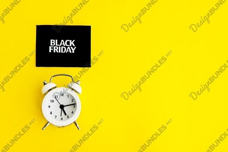White alarm clock and an inscription - black Friday