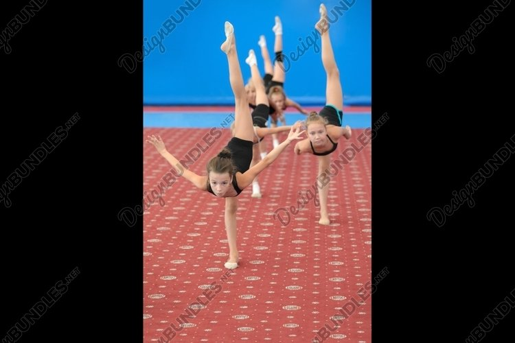 Young female gymnasts doing vertical leg-split example image 1
