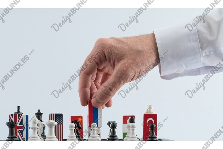 Politician's hand moves a chess piece. Political game. example image 1