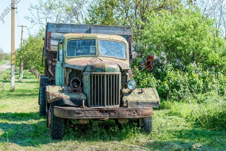 Old rusty truck on the green spring rural field example image 1