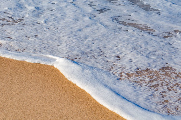 Picturesque beach, ocean waves run, footprints in the sand example