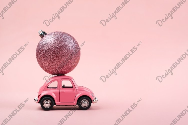 Christmas background with a pink retro toy car on pink example image 1