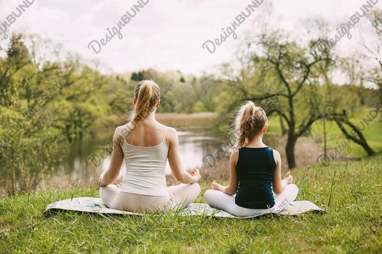 Mother and daughter sit in the Lotus position in the garden. example image 1