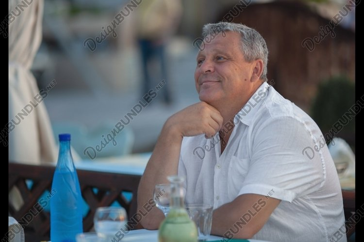Charming mature man in outdoor cafe example image 1