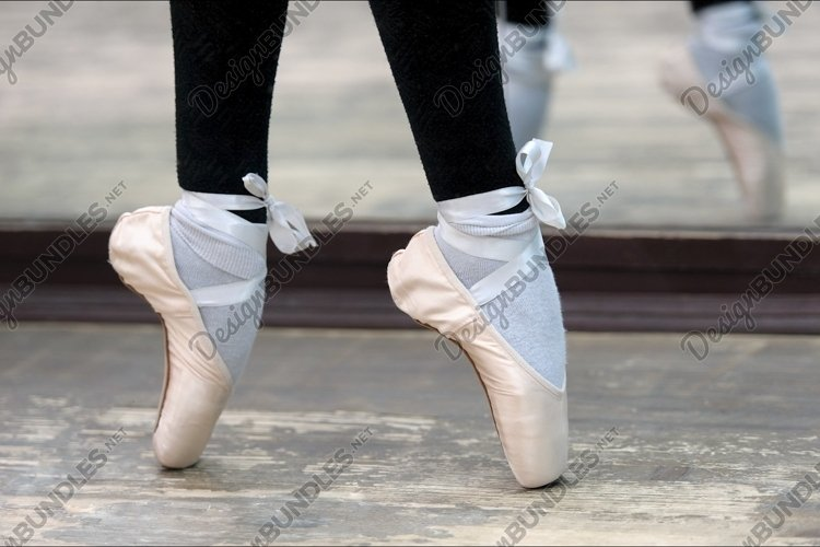 Close up view to ballerinas legs in pointes on wooden floor example image 1