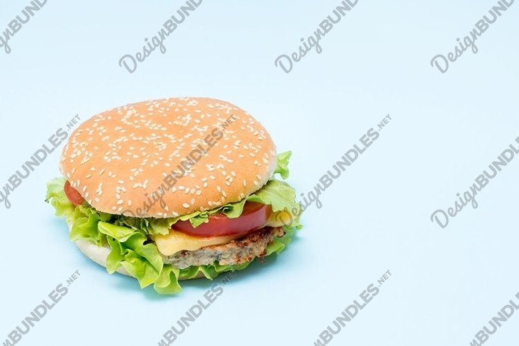 Cheeseburger with tomatoes and lettuce on a blue background example image 1