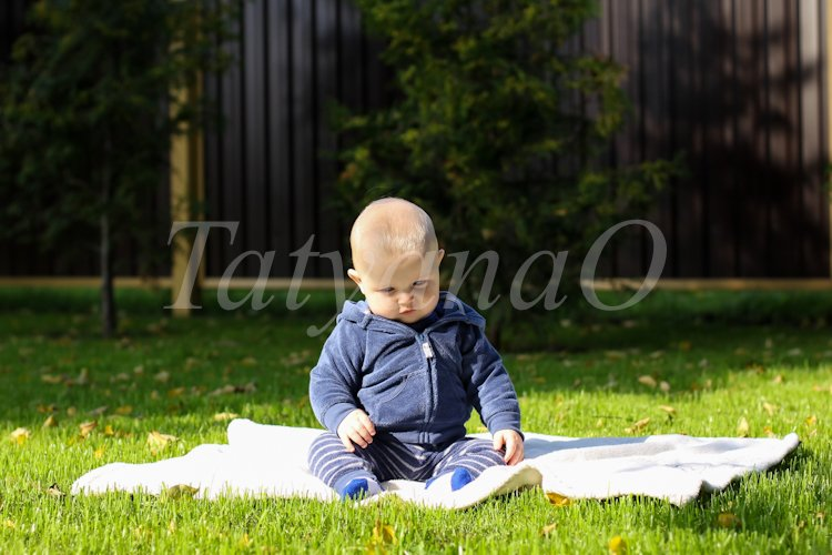 Portrait of a cute little boy sitting on a blanket example image 1