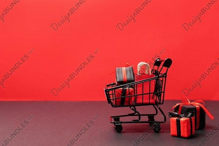 black paper bags and gift boxes in shopping cart on red example image 1
