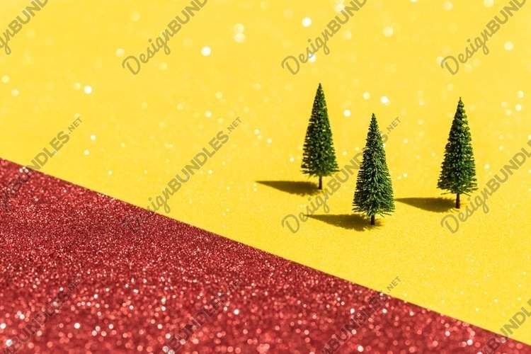 Three fir trees on glittering red yellow background.