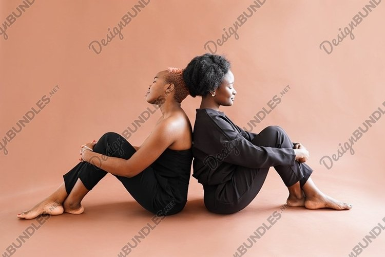 Couple african girls back to back sitting on the floor example image 1