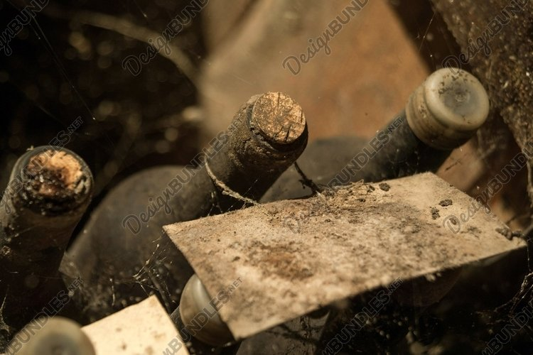 Old wine bottles in the web in the wine cellar example image 1