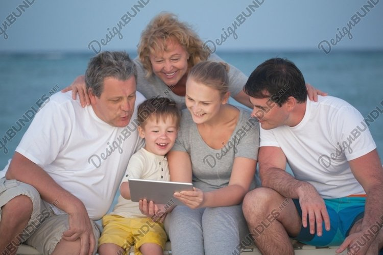 Happy big family with tablet PC on the beach example image 1