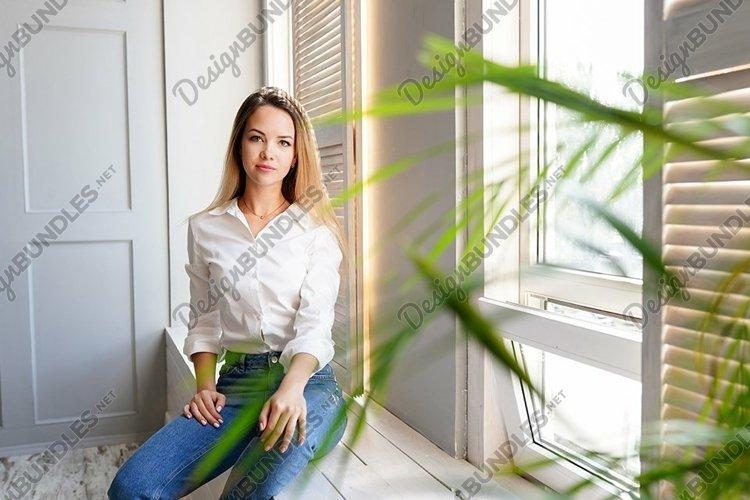 beautiful young girl sitting alone on the windowsill example image 1