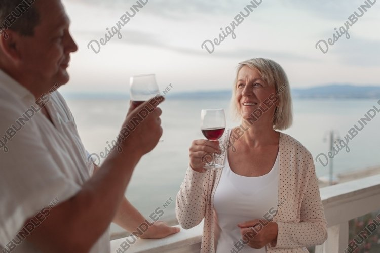 A smiling middle aged couple on a terrace close to the sea example image 1