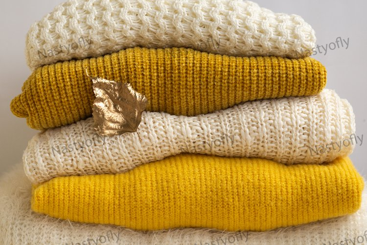 Pile of knitted clothes with autumn gold leaves