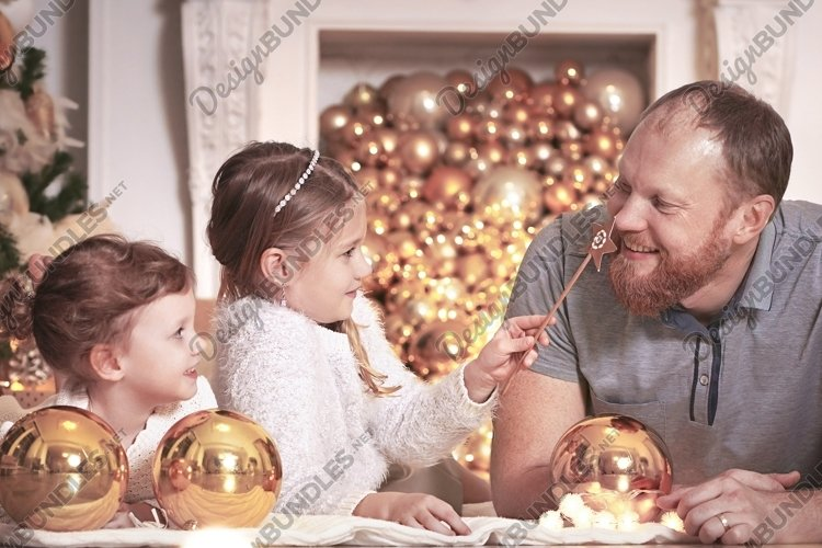 Happy family in Christmas night near christmas tree example image 1