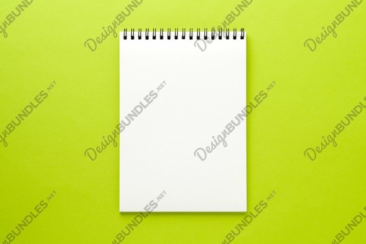Blank notepad white page on green desk, color background