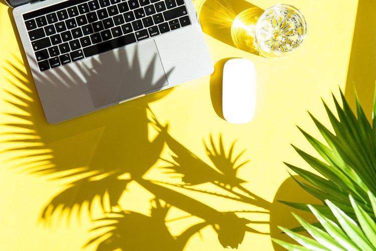 Trendy summer office workplace flat lay. Laptop sun shadow